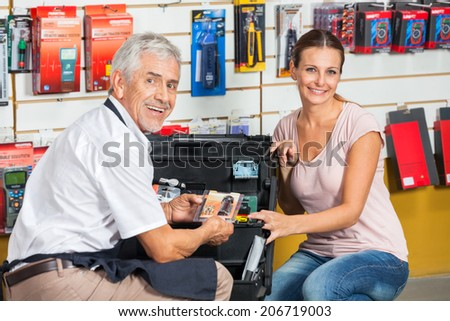 Portrait of smiling salesman assisting woman in hardware store