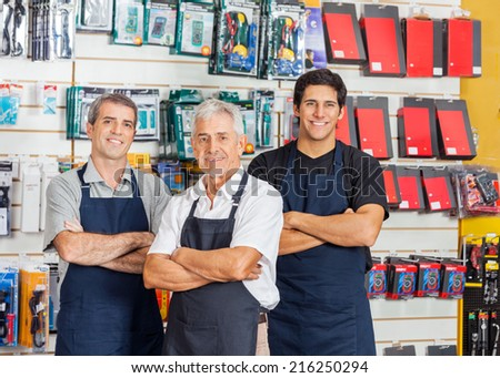 Portrait of smiling salesmen standing arms crossed in hardware shop - stock photo