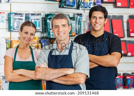 Portrait of smiling salespeople standing arms crossed in hardware shop - stock photo