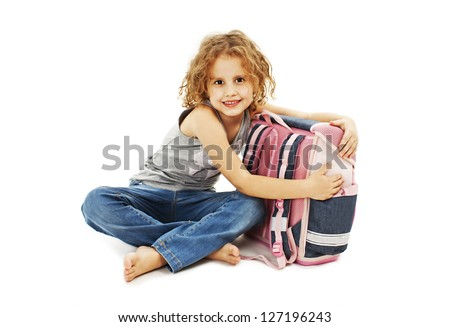 Portrait of smiling school girl hugging rucksack. Isolated on white background