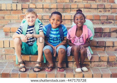 Portrait of smiling school kids sitting together on stairs at school - stock photo
