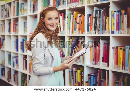 Portrait of smiling school teacher holding book in library at school