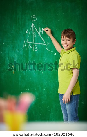 Portrait of smiling schoolboy looking at camera by the blackboard