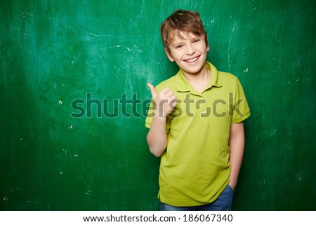 Portrait of smiling schoolboy showing thumb up while standing by the blackboard - stock photo
