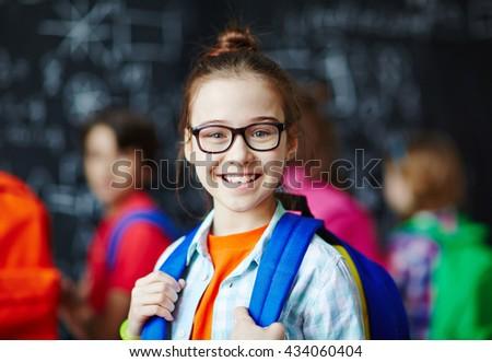 Portrait of smiling schoolgirl wearing eyeglasses - stock photo