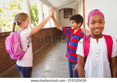 Portrait of smiling schoolgirl with friends high fiving in background at school corridor - stock photo