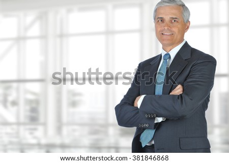 Portrait of smiling senior businessman standing against office window background while looking at camera. - stock photo