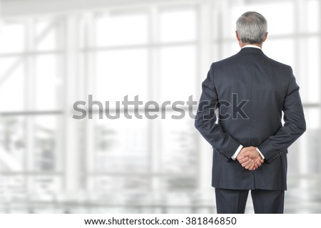 Portrait of smiling senior businessman standing looking out of office window with his hand behind his back. - stock photo