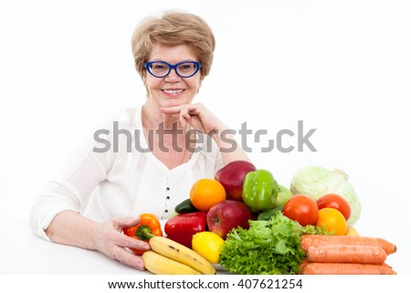 Portrait of smiling senior Caucasian woman with fresh vegetables and fruits on table, isolated on white background - stock photo