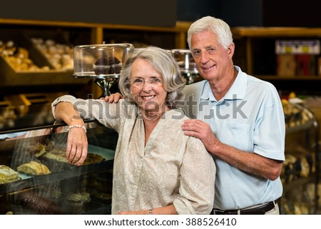 Portrait of smiling senior couple at the bakery store - stock photo