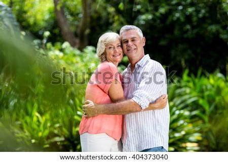 Portrait of smiling senior couple embracing at yard - stock photo