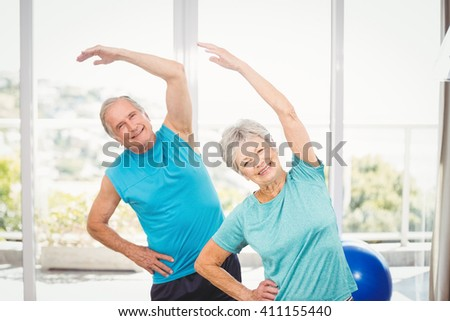 Portrait of smiling senior couple exercising at home - stock photo