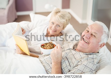 Portrait of smiling senior couple reading book while having breakfast on bed at home - stock photo