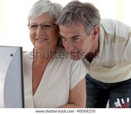 Portrait of smiling senior couple using a computer at home - stock photo