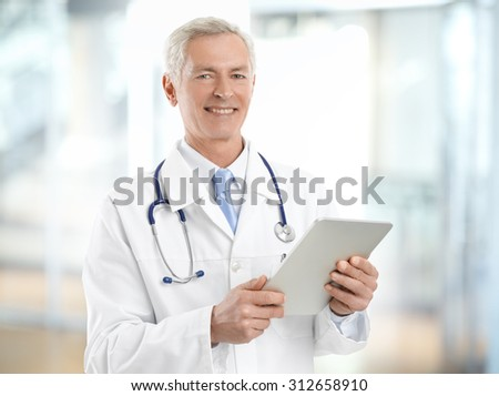 Portrait of smiling senior doctor holding hand digital tablet and standing at hospital.  - stock photo