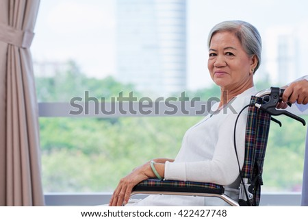Portrait of smiling senior lungs x-ray Vietnamese woman in wheelchair - stock photo