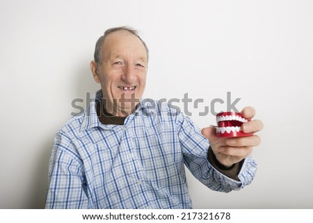 Portrait of smiling senior man holding teeth model against gray background - stock photo