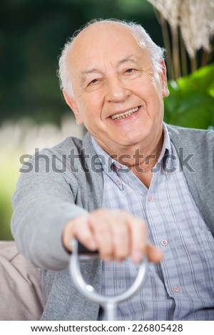 Portrait of smiling senior man holding walking stick while sitting on couch in nursing home porch