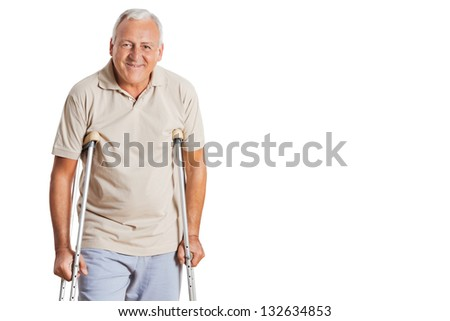 Portrait of smiling senior man on crutches standing over white background.