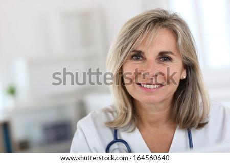 Portrait of smiling senior nurse in hospital - stock photo