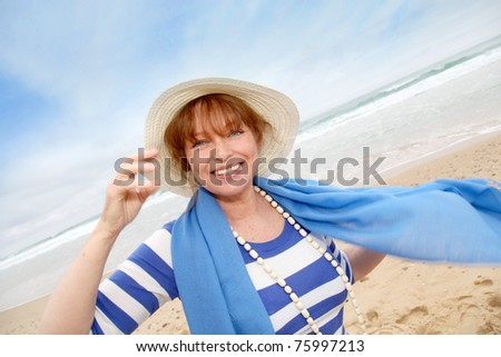 Portrait of smiling senior woman at the beach - stock photo