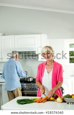 Portrait of smiling senior woman cutting vegetables in kitchen - stock photo