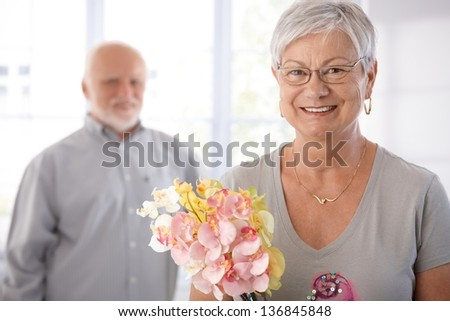 Portrait of smiling senior woman holding flowers, man at background. - stock photo