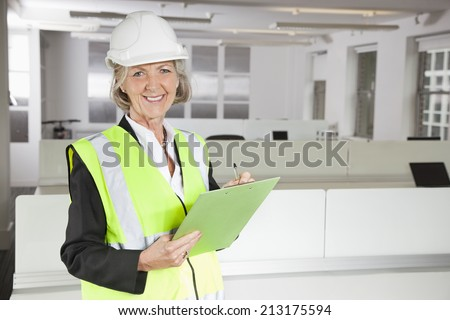 Portrait of smiling senior woman in reflector vest and hard hat holding clipboard at office - stock photo
