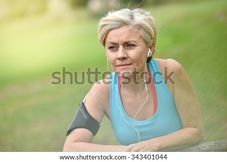 Portrait of smiling senior woman relaxing after exercising - stock photo