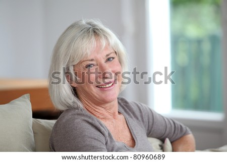 Portrait of smiling senior woman sitting in sofa
