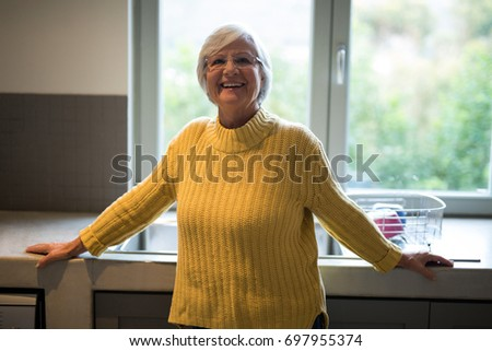 Portrait of smiling senior woman standing near kitchen worktop