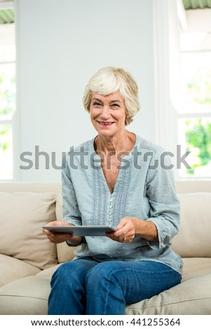 Portrait of smiling senior woman with digital tablet on sofa at home