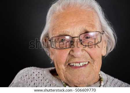 Portrait Of Smiling Senior Woman With Eyeglasses Over Grey Background