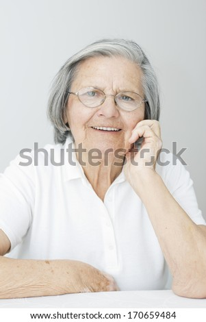Portrait of smiling  senior woman with hand on her chin looking at camera. - stock photo