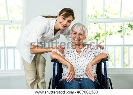 Portrait of smiling senior woman with nurse at health club - stock photo