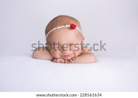 Portrait of smiling seven day old newborn baby girl. She is wearing a pearl and red rose headband and is sleeping on white, textured material. - stock photo