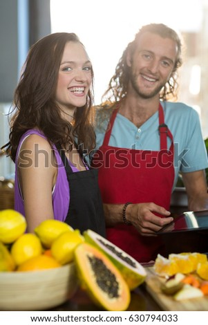 Portrait of smiling shop assistants standing at counter with digital tablet