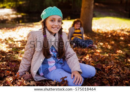 Portrait of smiling siblings sitting on field at park during autumn