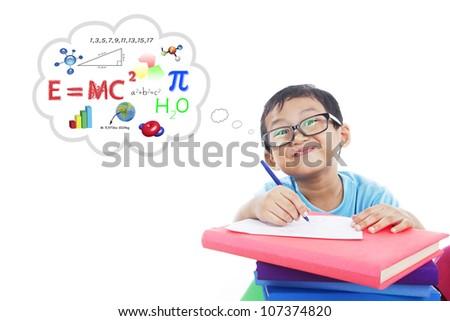 Portrait of smiling smart boy writes formula to solve physics formula on the paper - stock photo
