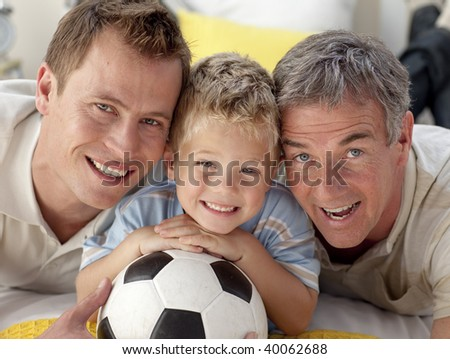 Portrait of smiling son, father and grandfather lying on floor - stock photo