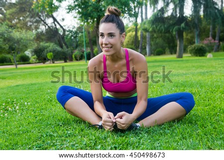 Portrait of smiling sportswoman in bright sportswear stretching in park on grass
