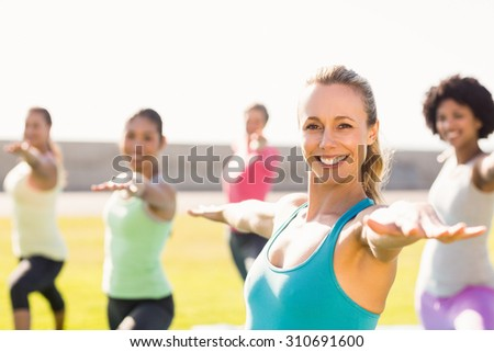 Portrait of smiling sporty blonde doing yoga in yoga class in parkland - stock photo