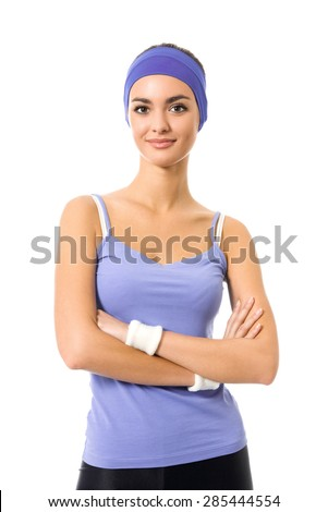 Portrait of smiling sporty brunette woman in violet sportswear, isolated against white background. Young female fitness instructor or personal trainer in crossed arms pose at studio. - stock photo