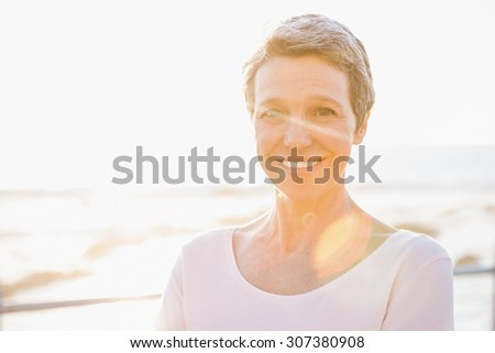 Portrait of smiling sporty woman at promenade on a sunny day - stock photo