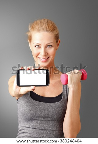 Portrait of smiling sporty woman holding a mobile phone with blank display and a dumbbell in her hand while standing at isolated background. - stock photo
