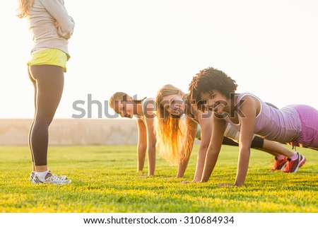 Portrait of smiling sporty women doing push ups during fitness class in parkland - stock photo