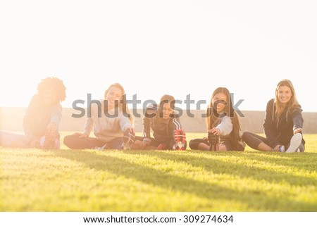 Portrait of smiling sporty women stretching during fitness class in parkland - stock photo