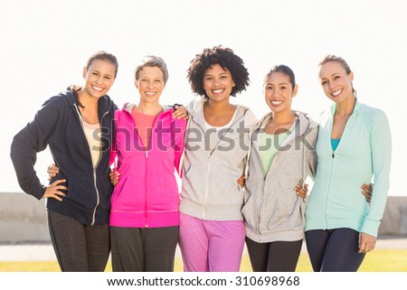 Portrait of smiling sporty women with arms around each other in parkland - stock photo