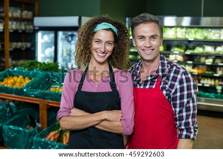 Portrait of smiling staffs standing together with arms crossed in organic section of supermarket