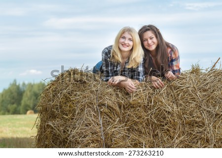 Portrait of smiling student friends are resting on large round grain straw bale - stock photo